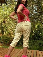 Buxom brunette in tight pants & high-heel sandals strips outside.