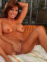 Cock starved Anilos Tara Holiday pleasures her needy milf pussy in bed