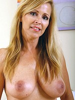 Blonde MILF with giant mature tits spreads her beaqver on the bed